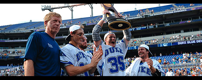 Triumphant: Coach John Danowski and the four team captains—seniors Sam Payton, Ned Crotty, Parker McKee, and Max Quinzani, from left— receive NCAA Championship trophy following Blue Devils' overtime win. Lance King