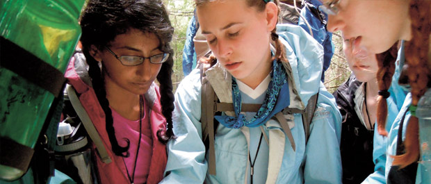 Roughing it: Kavya Durbha (in pink jacket) and her fellow PWILDers assess their location on a topographic map. Credit: Doug Clark