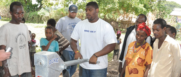Well wishers: Surrounded by teammates and villagers, sophomore offensive lineman Laken Tomlinson pumps the first buckets of clean water from the newly dug well. [Credit: Merrie Harding]