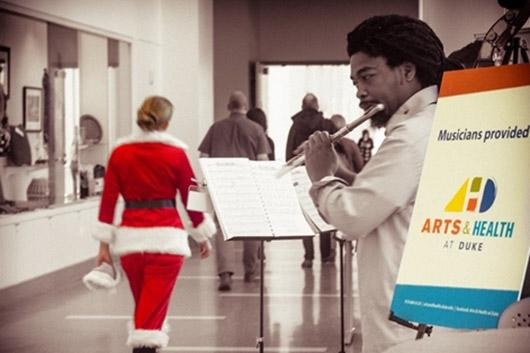 man playing flute with a woman dressed in a Santa Clause outfit walking down the hall.